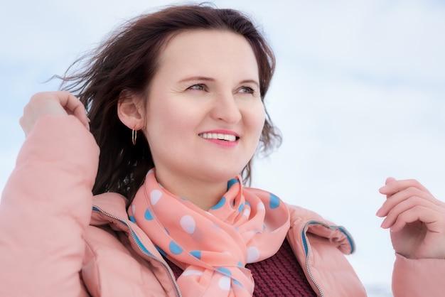 아름다운 미소와 바람에 나부끼는 곱슬머리 갈색 머리, 베이지색 재킷을 입고 목에 스카프를 두른 행복한 젊은 여성. 겨울에 야외에서 예쁜 여자의 초상화입니다.