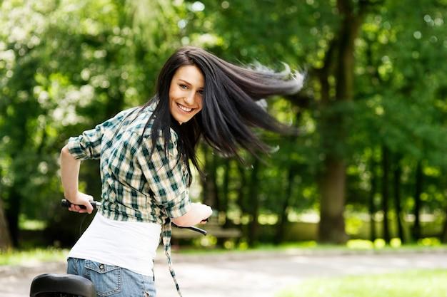 Счастливая молодая женщина с велосипедом в парке