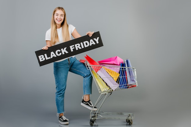 Happy young woman with black friday sign and pushcart with colorful shopping bags isolated over grey