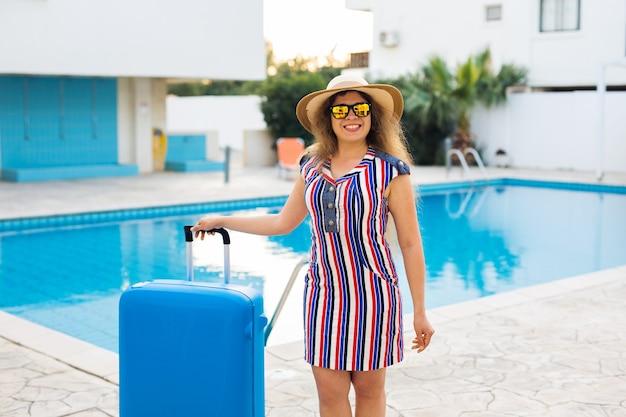 Счастливая молодая женщина с синим багажом прибывает на курорт