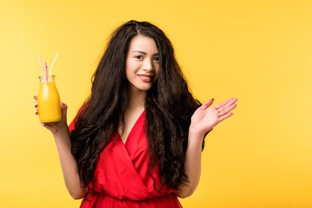 新鮮なスムージーのボトルを持つ幸せな若い女性。健康的な栄養減量ダイエット。コールドプレスビーガンリフレッシュメント