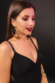 Happy young woman with bright make up and golden jewerly in black dress posing