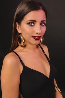 Giovane donna felice con trucco luminoso e jewerly dorato in posa nera del vestito