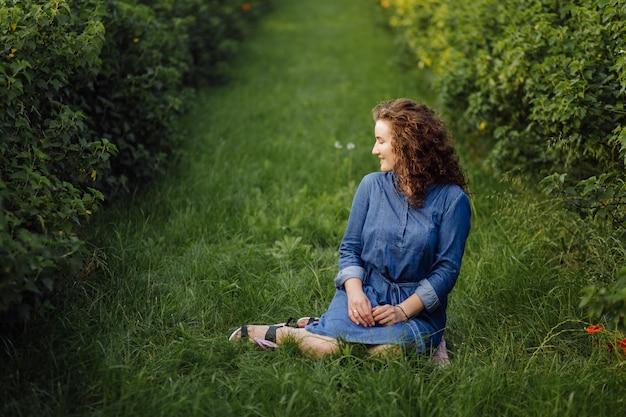 茶色の巻き毛のドレスを着て、庭で屋外でポーズ幸せな若い女