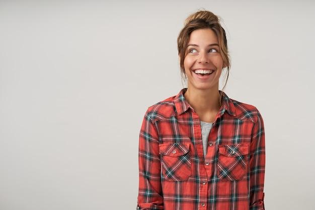 市松模様のシャツでポーズをとって、広い誠実な笑顔で元気に脇を見てカジュアルな髪型の幸せな若い女性