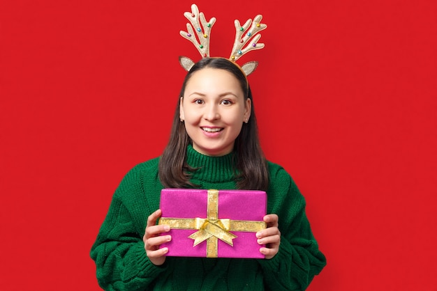Happy young woman with christmas deer antlers with gift on red background