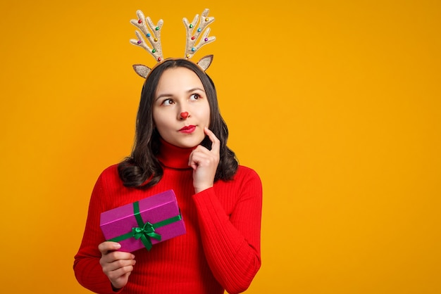 Happy young woman with christmas deer antlers with gift on yellow background.