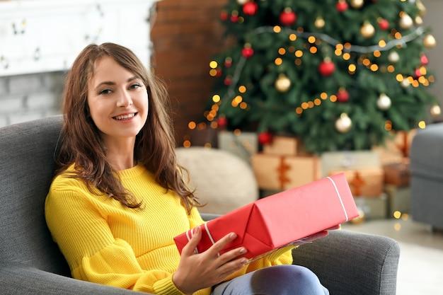 家でクリスマスプレゼントと幸せな若い女性