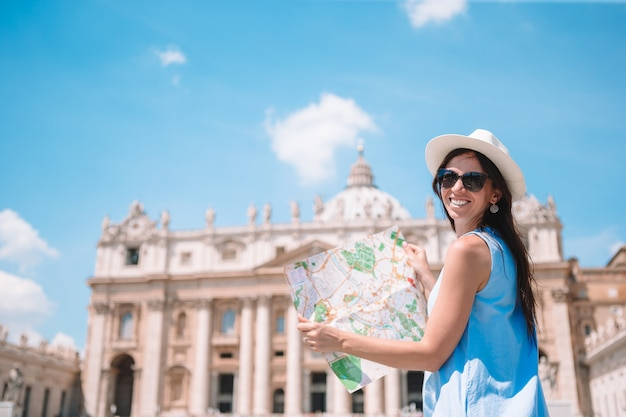 Happy young woman with city map in vatican city and st, peter's basilica church, rome, italy,