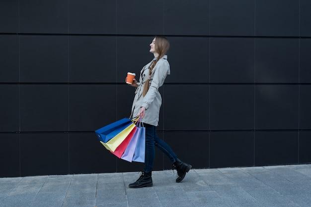 カラフルなバッグと紙コップが通りを歩いて幸せな若い女。背景に黒い壁