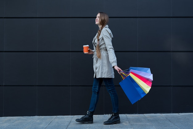 Happy young woman with colorful bags and paper cup walking on the street.