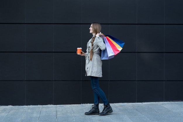Happy young woman with colorful bags and paper cup.