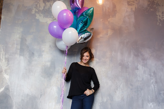 Happy young woman with colorful balloons near an empty gray concrete wall
