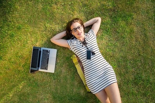 잔디에 화창한 날에 공원에서 컴퓨터와 함께 행복 한 젊은 여자