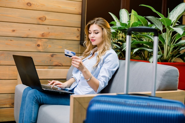 Happy young woman with credit card and laptop sitting on sofa at hotel lobby, booking the room