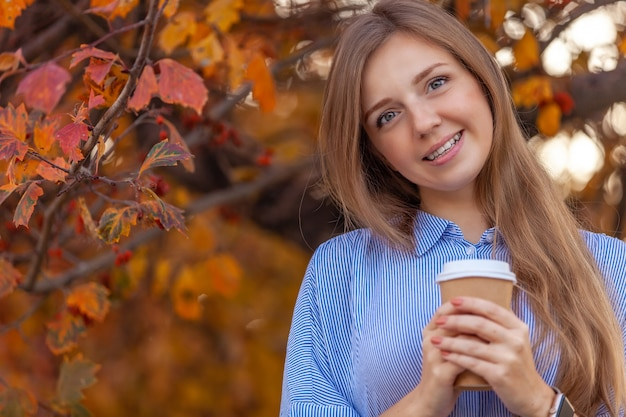 Happy young woman with cup of coffee to go on autumn red trees