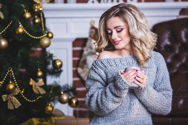 Happy young woman with cup of hot beverage near christmas tree