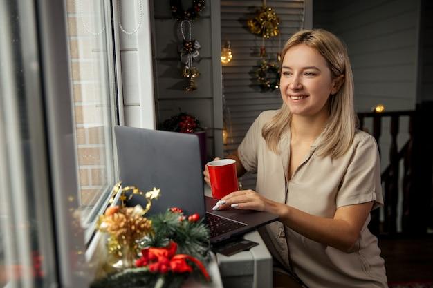 Счастливая молодая женщина с чашкой кофе, используя зум, чтобы поздравить с рождеством ее родственников. видеозвонки в режиме facetime с ноутбуком дома.