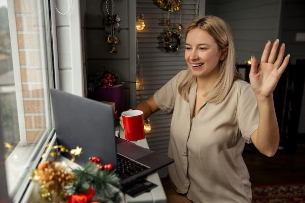 확대 / 축소를 사용 하여 그녀의 친척 메리 크리스마스를 축 하하는 커피 한잔과 함께 행복 한 젊은 여자. 집에서 노트북으로 얼굴 시간 화상 통화를 할 수 있습니다.
