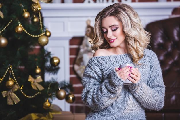 クリスマスツリーの近くのホットドリンクのカップを持つ幸せな若い女性