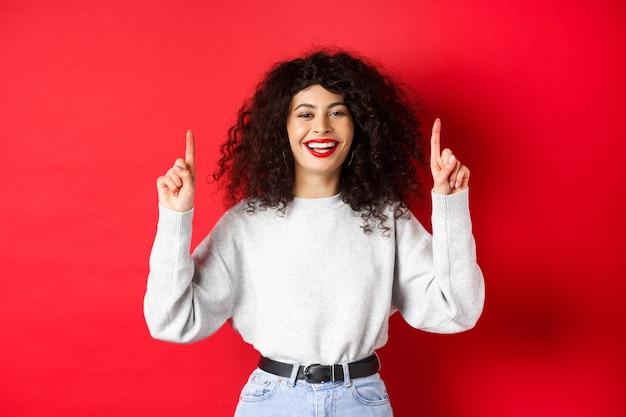 곱슬머리를 한 행복한 젊은 여성, 손가락을 가리키며 웃고, 완벽한 하얀 미소를 보여주고, 빨간 배경에 서서
