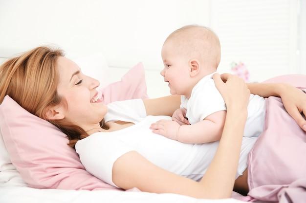 Счастливая молодая женщина с милым ребенком, лежа на кровати у себя дома