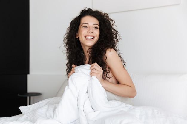 ベッドに座っている暗い巻き毛の幸せな若い女性