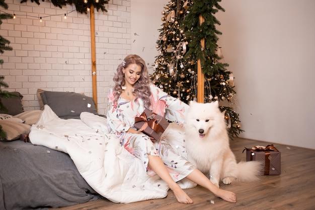 寝室で自宅でサモエド犬と幸せな若い女性