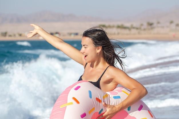 Una giovane donna felice con un cerchio di nuoto a forma di ciambella in riva al mare. il concetto di svago e intrattenimento in vacanza.