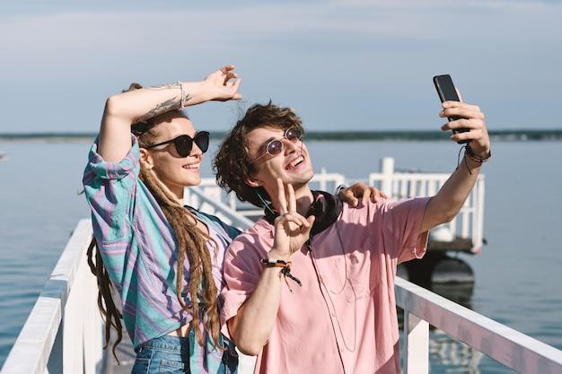 향취를 가진 행복한 젊은 여성과 연어 셔츠를 입은 그녀의 남자친구가 부두에 서서 소셜 미디어를 위해 셀카를 찍는다