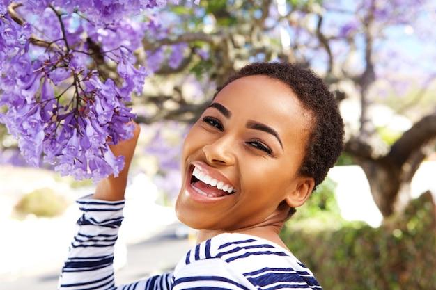 ツリーに花の幸せな若い女性