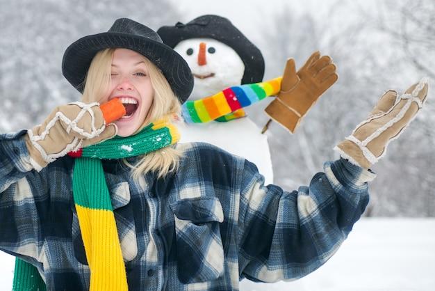 雪だるまの面白いニンジンの鼻を持つ幸せな若い女性。