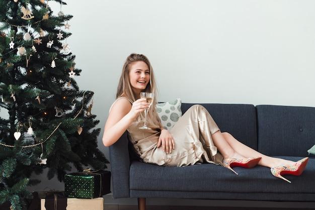 Счастливая молодая женщина с бокалом шампанского позирует у елки, глядя в камеру