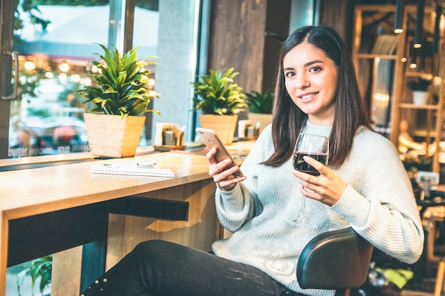 Happy young woman with glass of wine or glintwine checking the phone