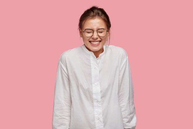 분홍색 벽에 포즈 안경 행복 한 젊은 여자