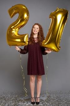 Felice giovane donna con palloncini dorati che celebra il suo compleanno