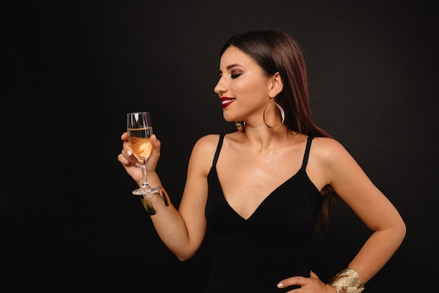 Happy young woman with golden jewerly in black dress drinking champagne