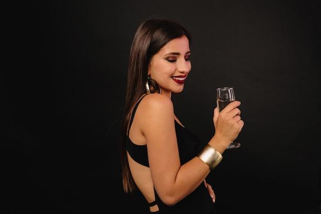 Felice giovane donna con gioielli d'oro in abito nero bevendo champagne