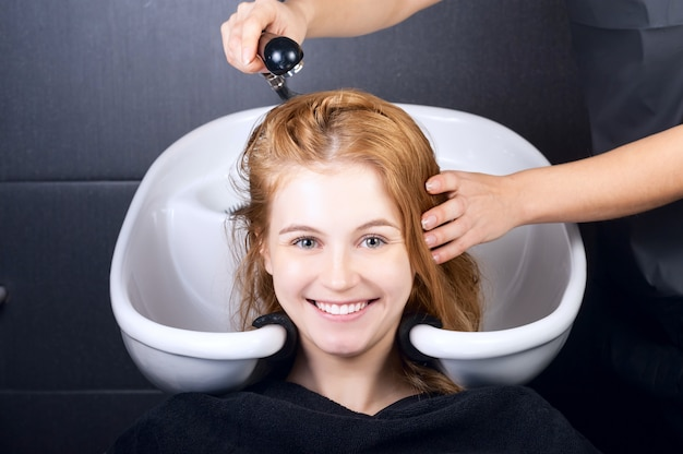 Happy young woman with hairdresser