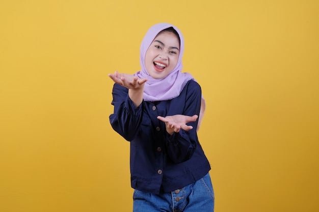 幸せな表情の幸せな若い女性は、黄色のヒジャーブとカジュアルな服を着て彼女の手に何かを示しています
