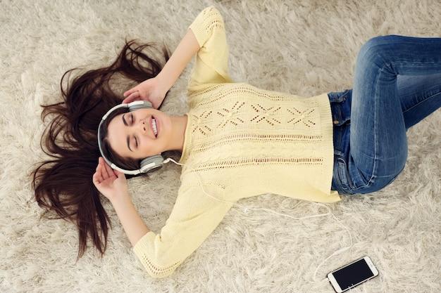 Счастливая молодая женщина с наушниками, слушающая музыку на ковре дома