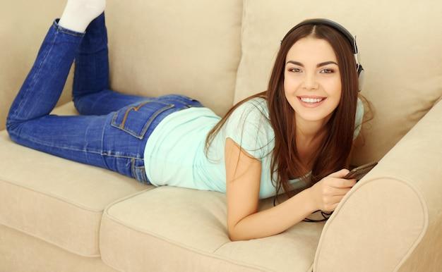 헤드폰 집에서 소파에서 음악을 듣고 행복 한 젊은 여자