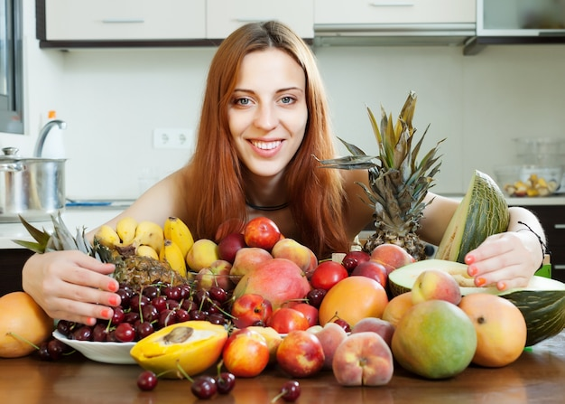 Happy young woman with heap of fruits