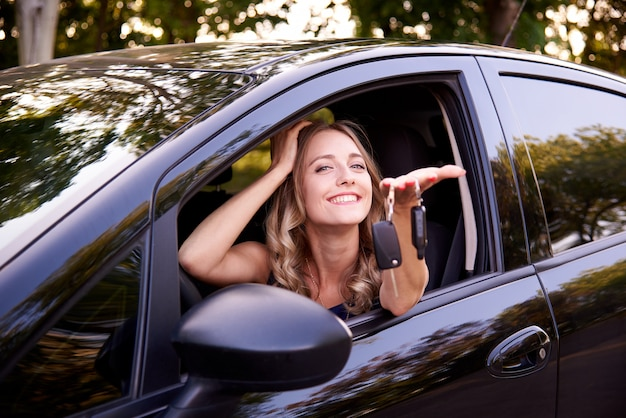 Happy young woman with keys in auto.