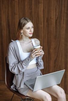 노트북과 커피가 앉아 있는 행복한 젊은 여성