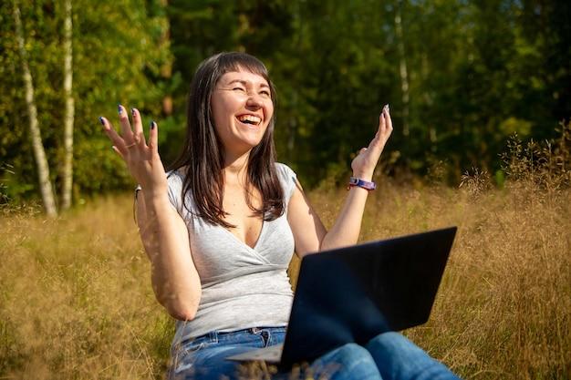 Счастливая молодая женщина с ноутбуком на солнечной лужайке фрилансер работает на природе, студент учится удаленно