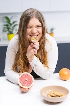 Счастливая молодая женщина с длинными светлыми волосами, используя блендер на современной кухне