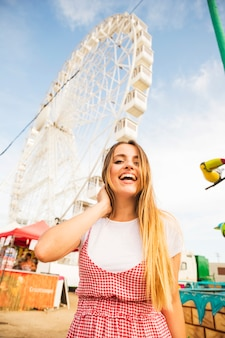 Happy young woman with long blonde hair standing in front of ferris wheel