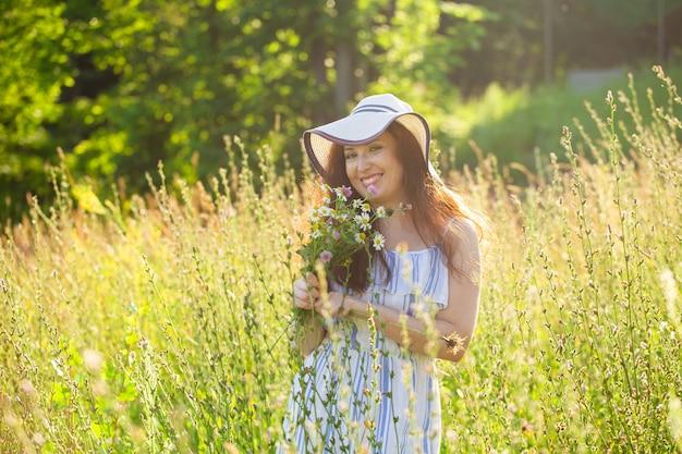 帽子とドレスを着た長い髪の幸せな若い女性は、晴れた日に夏の森を歩いている間、植物に向かって手を引っ張る。夏の喜びのコンセプト