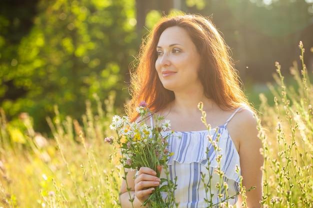 帽子とドレスを着た長い髪の幸せな若い女性は、晴れた日に夏の森を歩いている間、植物に向かって手を引っ張る。夏の喜びのコンセプト Premium写真